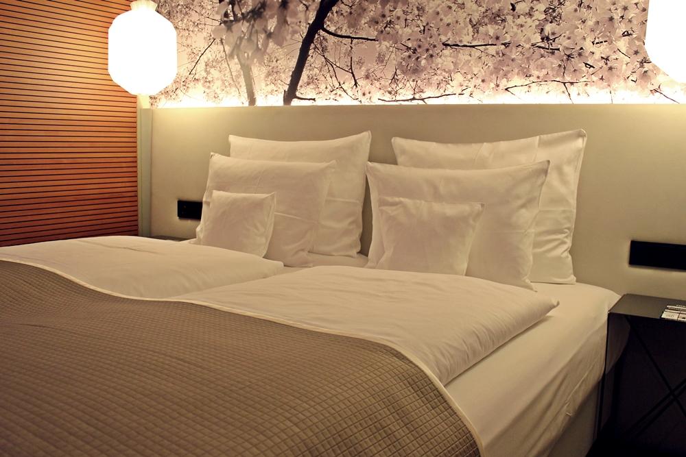 Bett mit vielen Kissen im me and all hotel düsseldorf